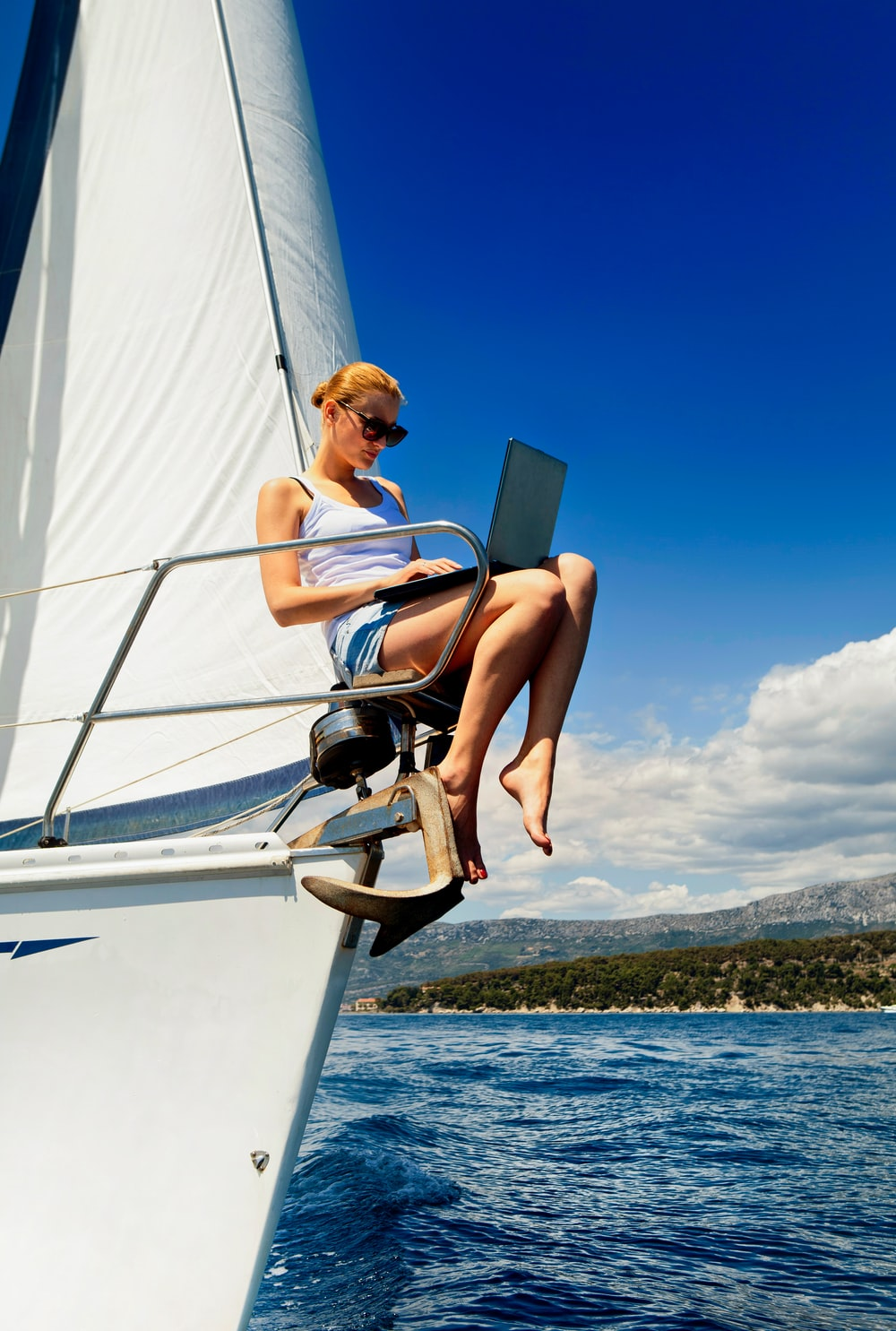 Working on the move. Young woman with laptop computer writing while sailing on the yacht on the ocean.
